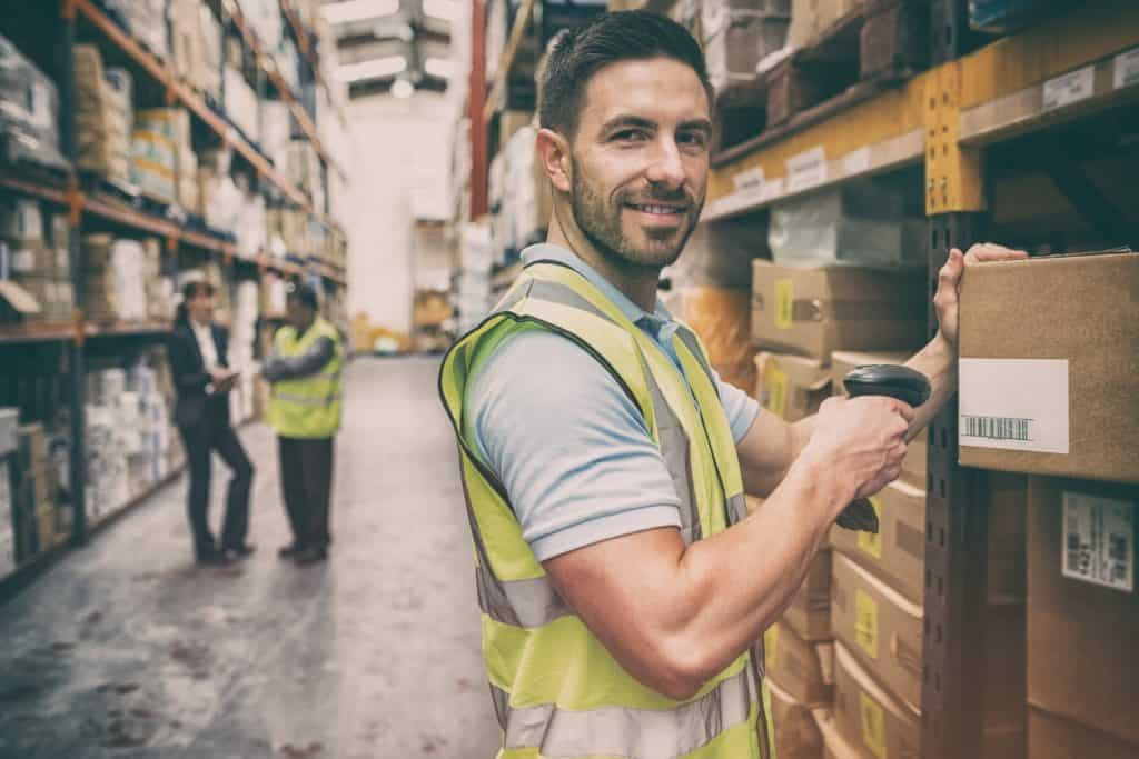 fulfillment Warehouse worker scanning box while smiling at camera