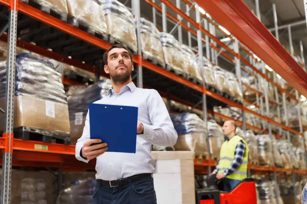 businessman with clipboard at warehouse