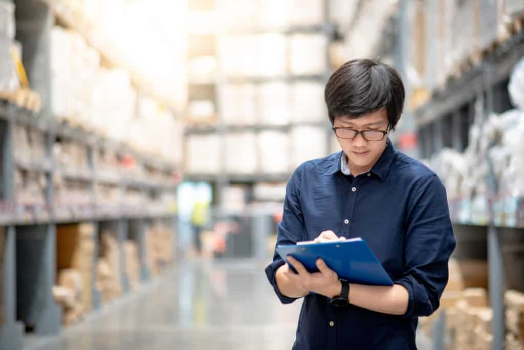 Young Asian man doing stocktaking of product in cardboard box on shelves in warehouse by using clipboard and pen. physical inventory count concept